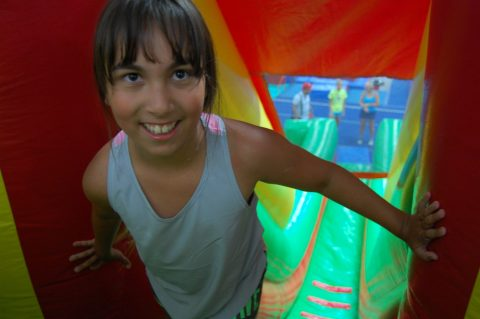 Smiling Nadia climbs up a slide at her summer camp.