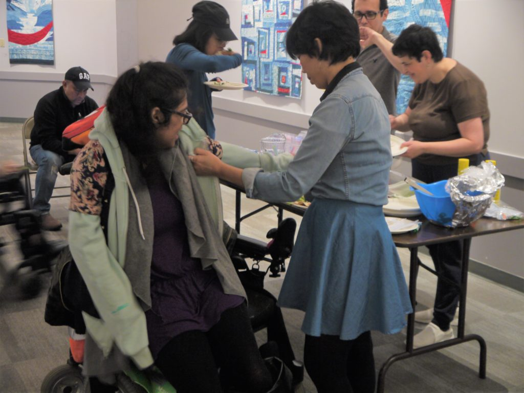 Karen helping a participant with adapted fashion.